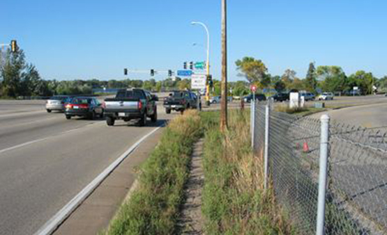 Traffic on University Avenue, chain link fence shown